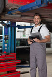 Mechanic Posing Under the Car with a Digital Tablet. Mechanic standing under the car and holding a digital tablet. Three quarter length shot in auto repair shop Stock Photo