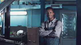 Mechanic posing in uniform. Young african mechanic in uniform standing with crossed arms in workshop stock video footage