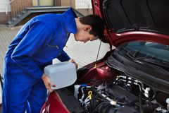 Mechanic pouring antifreeze into windscreen water tank Stock Photo