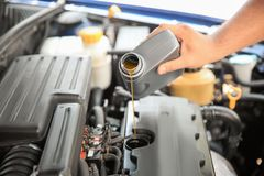 Mechanic pouring oil into car engine royalty free stock photography