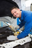 Mechanic pouring oil into car Stock Images