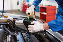 Mechanic pouring oil into car. At the repair garage Stock Images