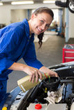 Mechanic pouring oil into car. At the repair garage royalty free stock photo