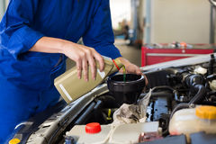 Mechanic pouring oil into car Stock Photography