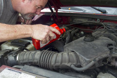 A Mechanic Pouring Oil In A Older Vehicle Stock Photo