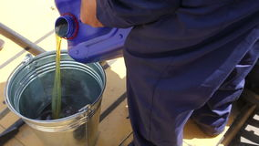 Mechanic pours oil from the big blue can inro bucket. Combine technical services. mechanic pours oil from the big blue can inro bucket stock video