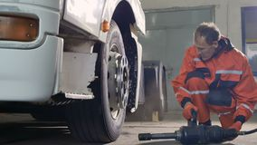 Mechanic preparing to unscrew the tire with screwdriver. Auto mechanic uses pneumatic screwdriver for repairing the tire of truck. Professional worker unscrew stock footage