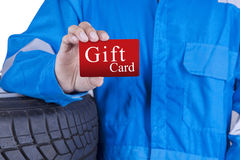 Mechanic presenting a gift card. Closeup of male mechanic with blue uniform standing near tires and showing a gift card Stock Images