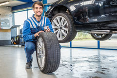 Mechanic Pressing Gauge Into Tire Tread In Garage Royalty Free Stock Photo