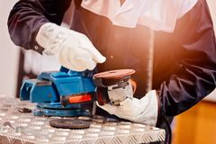 Mechanic in protective gloves changing cutting disc Royalty Free Stock Image