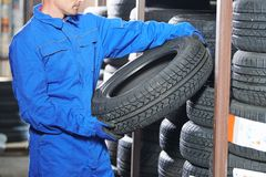Mechanic pulls tire from the tyre store warehouse. Mechanic in blue overalls pulls tire in the tyre store warehouse Stock Photos