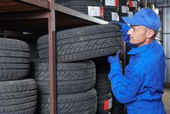 Mechanic pulls tire from the tyre store warehouse. Mechanic in blue overalls pulls tire in the tyre store warehouse Stock Image