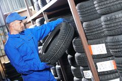 Mechanic pulls tire from the tyre store warehouse. Mechanic in blue overalls pulls tire in the tyre store warehouse Stock Photography