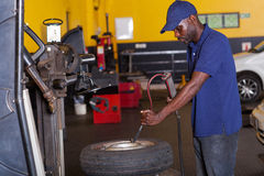 Mechanic pumping tyre. African auto mechanic pumping car tyre Stock Photography