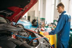 Mechanic pumps freon into the conditioning system royalty free stock images