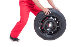 Mechanic pushing car wheel on white background Royalty Free Stock Photo
