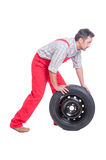 Mechanic pushing a new car wheel Stock Images