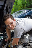 Mechanic Reaching. Mechanic looking up as he reaches to change the spark plugs in his car Royalty Free Stock Photos