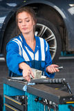Mechanic, reaching for tools on a tool trolley in a garage Stock Photography