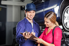 Mechanic Receiving Sign On Invoice From Customer. Male mechanic receiving sign on invoice from female customer in garage Royalty Free Stock Images