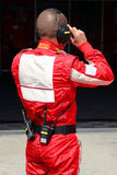 Mechanic in red overall. Before race box Stock Images