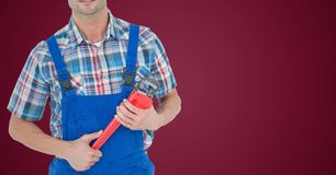 Mechanic with red wrench against maroon background Royalty Free Stock Photo