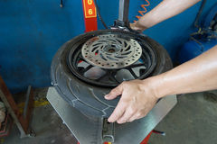 Mechanic removes tire closeup Stock Images