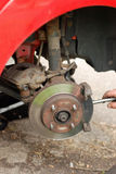 Mechanic removing brake pads from old disc brake. Stock Photos