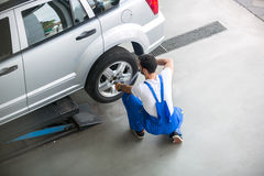 Mechanic removing a tire from a car Royalty Free Stock Image