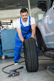 Mechanic repair and  pushing a black tyre Royalty Free Stock Photo