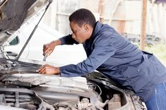 Mechanic repaire a car . Mechanic repairs the engine of a car in her workshop stock photo