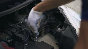Mechanic repairing car engine, fixing automotive battery, breakage under hood. Stock footage stock video footage