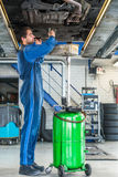 Mechanic Repairing Car On Hydraulic Lift In Automobile Shop Stock Image