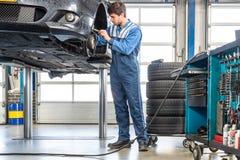 Mechanic Repairing Car On Hydraulic Lift. Male mechanic repairing car on hydraulic lift in garage Royalty Free Stock Photos