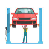 Mechanic repairing a car lifted on auto hoist Royalty Free Stock Photography