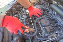 The mechanic is repairing the car. The mechanic`s hands on the background of the open bonnet repairs the details. Auto Repair and care Concept stock photo