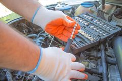 The mechanic is repairing the car. The mechanic`s hands on the background of the open bonnet repairs the details. Auto Repair and care Concept royalty free stock images