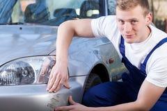 Mechanic repairing car scratching Royalty Free Stock Image