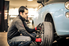 Mechanic. Repairing a car wheel royalty free stock image