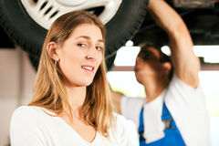 Mechanic repairing car of woman Royalty Free Stock Images