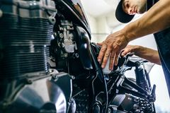 Mechanic repairing customized motorcycle stock photography
