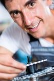 Mechanic repairing gears of bicycle. In workshop stock image