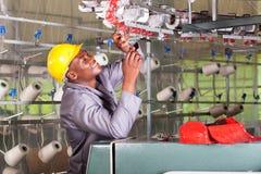 Mechanic repairing loom. African american textile mechanic reapairing weaving loom royalty free stock image