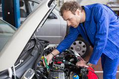 Mechanic repairing a car in a workshop or garage Royalty Free Stock Photography