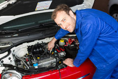 Mechanic repairing a car in a workshop or garage Stock Photo