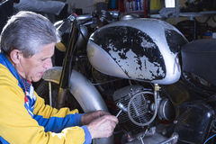 Mechanic repairing a motorcycle engine Stock Photography