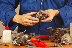 Mechanic repairing parts of the automobile engine in workshop Royalty Free Stock Image