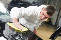 Mechanic repairing and polishing car. Auto mechanic worker polishing car bonnet with wiper at automobile repair and renew service station shop Stock Images