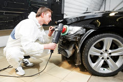 Mechanic repairing and polishing car headlight stock photo