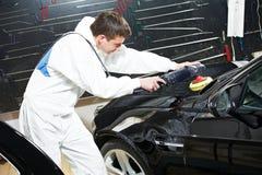 Mechanic repairing and polishing car headlight Royalty Free Stock Photo